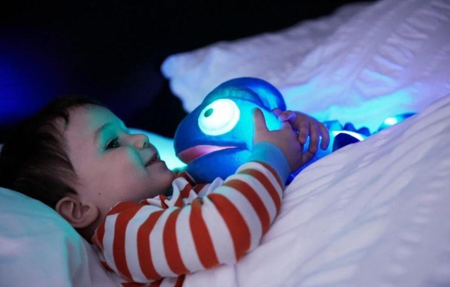 Lille dreng ligger og holder om en sanselampe ved sengetid